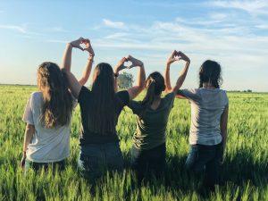 girl friends in field holding hands